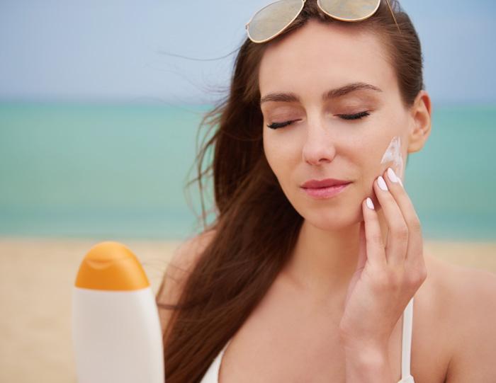 Γυναίκα σε παραλία βάζει αντηλιακό στο μάγουλο του προσώπου της