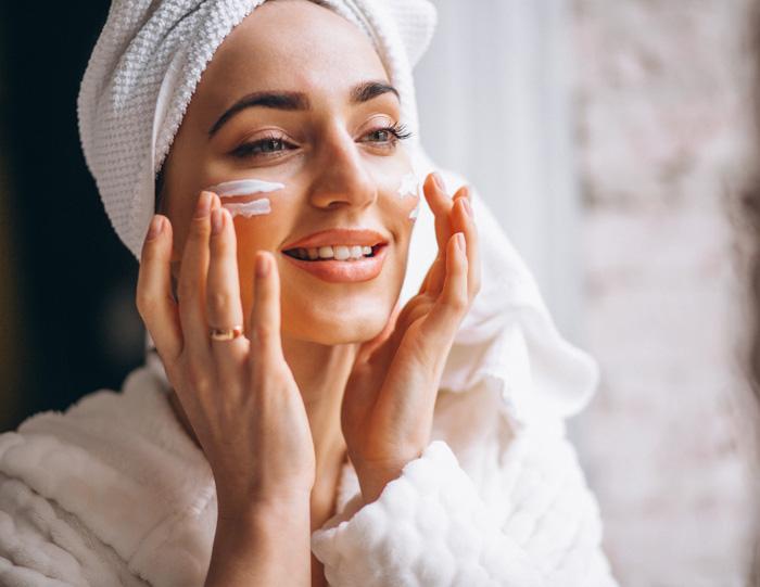 Γυναίκα με μπουρνούζι εφαρμόζει ενυδατική κρέμα στο πρόσωπό της για λαμπερή επιδερμίδα