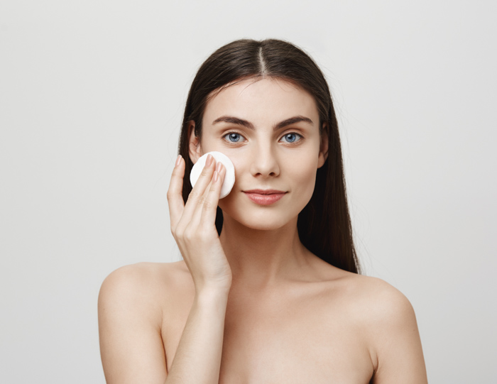 Μελαχρινή γυναίκα αφαιρεί το make up απ' το πρόσωπό της με βαμβακερό δίσκο ντεμακιγιάζ
