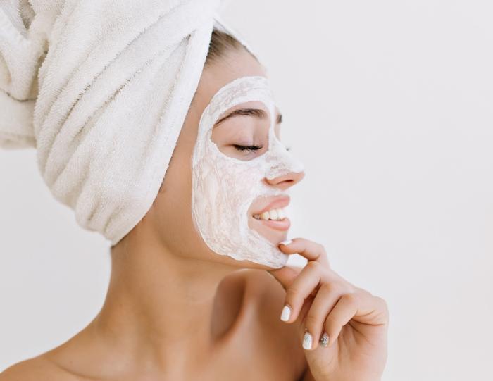 Χαμογελαστή γυναίκα με πετσέτα στο κεφάλι φοράει μάσκα ομορφιάς για λαμπερό δέρμα προσώπου